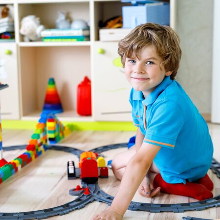 Adorable little blond kid boy playing with colorful plastic blocks and creating train station. Child having fun with building railway toys at home