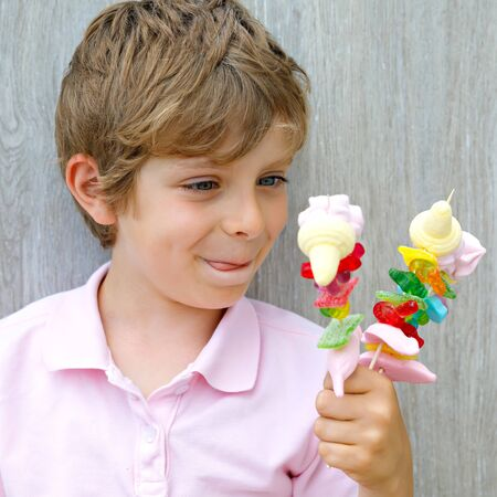 Happy little kid boy holding marshmallow skewer in hand. Child with different unhelthy colorful sweets