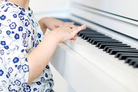 Closeup of hands little kid girl playing piano in living room or music school. Preschool child having fun with learning to play music instrument. Education, skills concept.