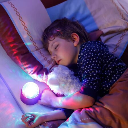 Little preschool kid boy sleeping in bed with colorful lamp. School child dreaming and holding plush toy. Kid angry of darkness