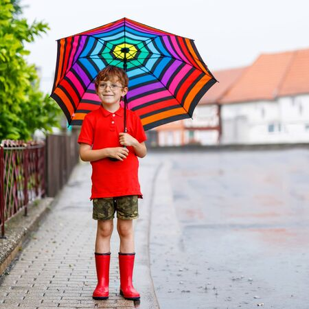 Happy kid boy wearing red rain boots and walking with colorful umbrella on city street. Child with glasses on summer day. happy kid during heavy summer shower rain Reklamní fotografie