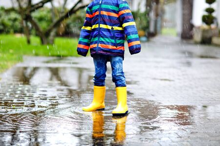 Close-up of kid wearing yellow rain boots and walking during sleet, rain and snow on cold day. Child in colorful fashion casual clothes jumping in a puddle. Having fun outdoors.