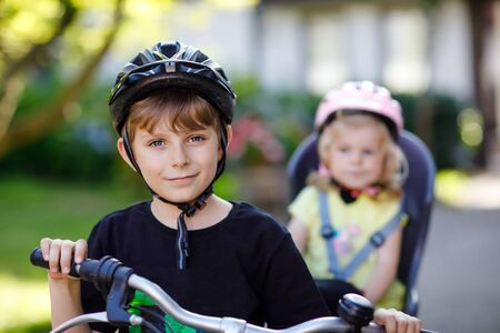 Portrait of little toddler girl with security helmet sitting in bike seat of brother. Kid boy on bicycle with lovely sister. Safe and child protection concept. Family weekend activity trip.