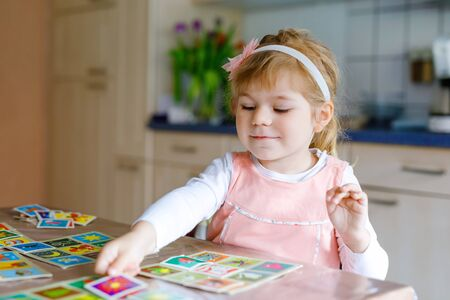 Adorable cute toddler girl playing picture card game. Happy healthy child training memory, thinking. Creative indoors leisure and education of kid during pandemic coronavirus covid quarantine disease