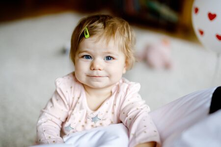 Lovely cute beautiful little baby girl playing with educational toys at home or nursery. Happy healthy child having fun with colorful different toys. Toddler learning different skills Reklamní fotografie