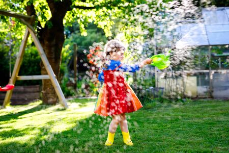 Beautiful little toddler girl in yellow rubber boots and colorful dress watering spring flowers with kids water can. Happy child helping in family garden, outdoors, having fun with splashing Reklamní fotografie