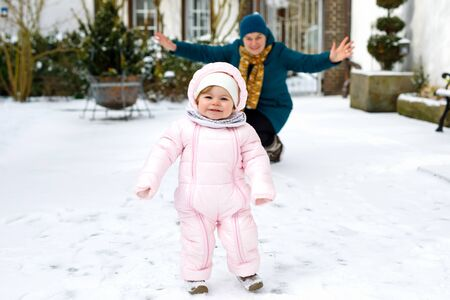 Adorable little baby girl making first steps outdoors in winter with mother. Cute toddler learning walking. Reklamní fotografie