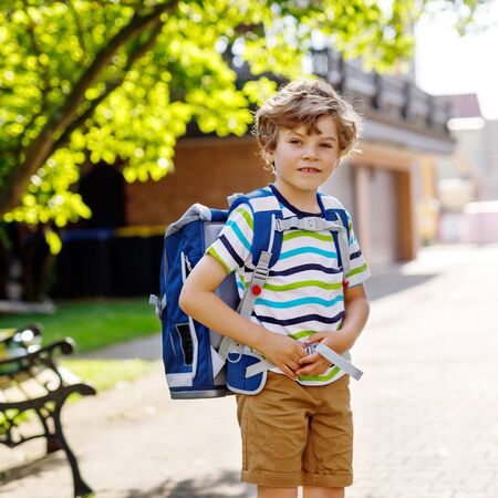 Happy little kid boy with glasses and backpack or satchel on his first day to school or nursery. Child outdoors on warm sunny day, Back to school concept.