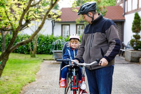 Portrait of little toddler girl with security helmet on the head sitting in bike seat and her father with bicycle. Safe and child protection concept. Family and weekend activity trip. 写真素材