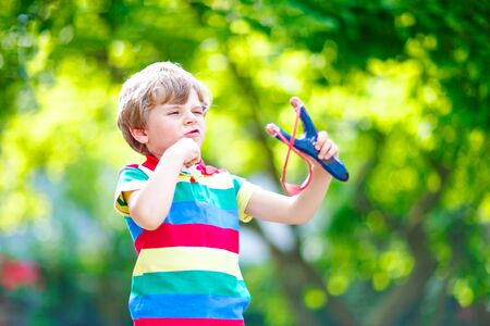 Funny little kid boy shooting wooden slingshot against green tree background. Child having fun in summer Foto de archivo