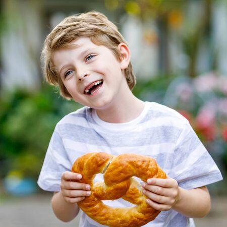 Adorable little kid boy eating huge big bavarian german pretzel. Happy blond child with teeth gap enjoying tasteful tratditional bread. Healthy food for happy kids. Фото со стока