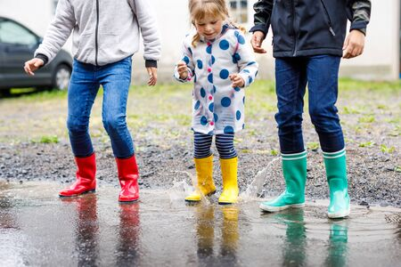 Close-up of three children, toddler girl and two kids boys wearing red, yellow and green rain boots and walking during sleet. Happy siblings jumping into puddle. Having fun outdoors, active family