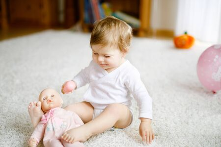 Lovely cute beautiful little baby girl playing with toy doll at home or nursery. Happy healthy child having fun with different toys. Toddler learning different skills.