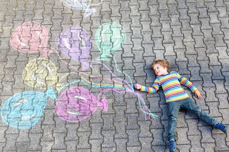 Little happy blond kid having fun with colorful air balloons picture drawing with colorful chalks. Creative leisure for children outdoors in summer, celebrating birthday. Chalk on asphalt