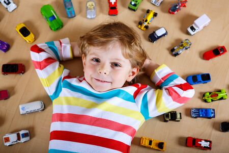 Lovely blond kid boy playing with lots of toy cars indoor. Happy healthy child boy having fun during pandemic coronavirus quarantine disease. Child alone at home, closed nursery