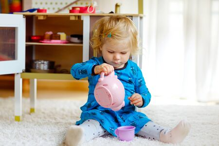 Adorable cute little toddler girl playing with toy kitchen Happy healthy baby child having fun with role game, playing with crockery teapot at home or nursery. Active daughter with toy.