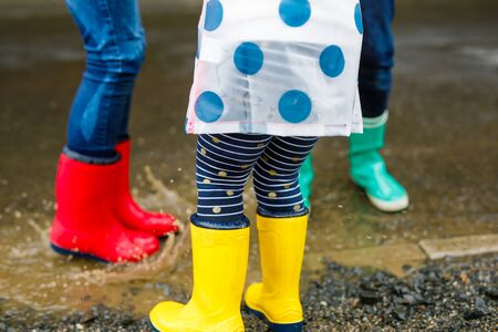 Close-up of three children, toddler girl and two kids boys wearing red, yellow and green rain boots and walking during sleet. Happy siblings jumping into puddle. Having fun outdoors, active family.