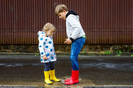 Two children, toddler girl and kid boy wearing red and yellow rain boots, walking during sleet. Happy siblings, brother and sister jumping into puddle. Having fun outdoors, active family outdoors