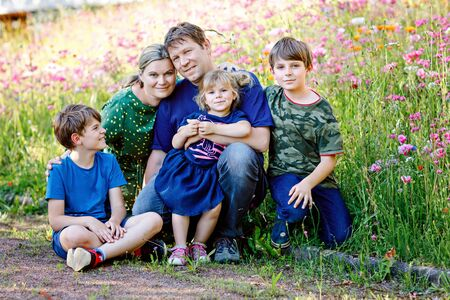 Summer portrait of parents with three children. Mother, father, two kids brothers boys and little cute toddler sister girl having fun together on flower meadow. Happy family of five