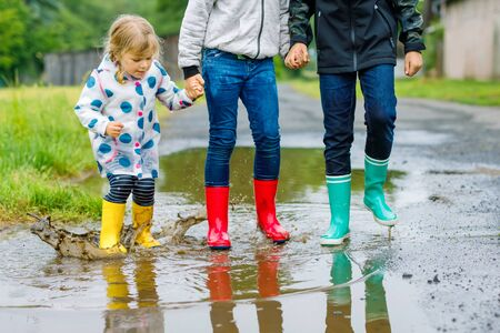 Three children, toddler girl and two kids boys wearing red, yellow and green rain boots and walking during sleet. Happy siblings jumping into puddle. Having fun outdoors, active family
