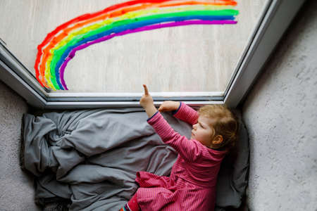 Adoralbe little toddler girl with rainbow painted with colorful window color during pandemic coronavirus quarantine. Child painting rainbows and hearts around the world with words Lets all be well.