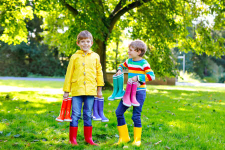 Two little kids boys, cute siblings with lots of colorful rain boots. Children in different rubber boots and jackets. Footwear for rainy fall. Healthy twins and best friends having fun outdoors