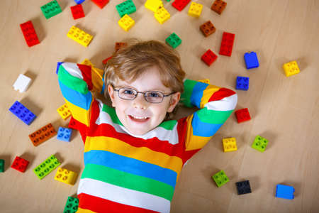 Little blond child with glasses playing with lots of colorful plastic blocks indoor. Kid boy wearing colorful shirt and having fun with building and creating