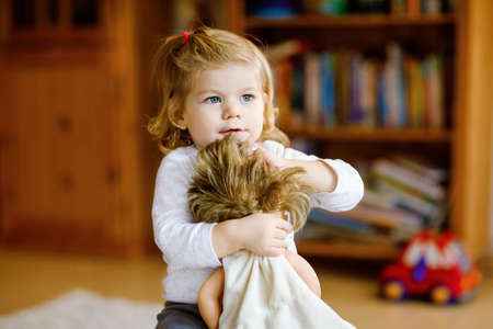 Adorable cute little toddler girl playing with doll. Happy healthy baby child having fun with role game, playing mother at home or nursery. Active daughter with toy Foto de archivo