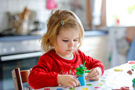 Adorable cute little toddler girl with colorful clay. Healthy baby playing and creating toys from play dough. Small kid molding modeling clay and learning Stock Photo
