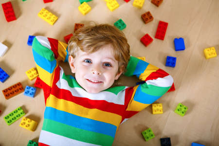 Little blond child playing with lots of colorful plastic blocks indoor. Kid boy wearing colorful shirt and having fun with building and creating