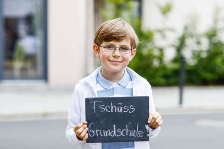 Happy little kid boy with backpack or satchel and glasses. Schoolkid on the way to school. Healthy adorable child outdoors On desk Bye elementary school in German. Schools out