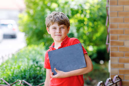 Happy little kid boy with glasses and backpack or satchel. Schoolkid on the way to school. Healthy adorable child outdoors. Empty chalk desk in hands for copyspace and free text. Back to school.