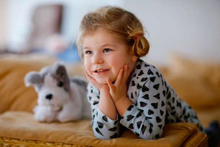 Cute little toddler girl in nightwear pajamas watching cartoons or movie on tv. Happy healthy baby child at home. Foto de archivo