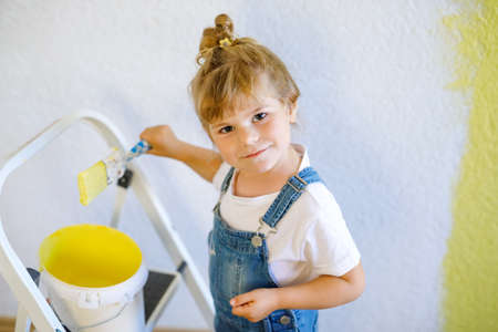 Adorable little toddler girl painting the wall with color in new house. Family repair apartment home. Happy baby child paints the wall, choosing color with palette, having fun with brush, indoors
