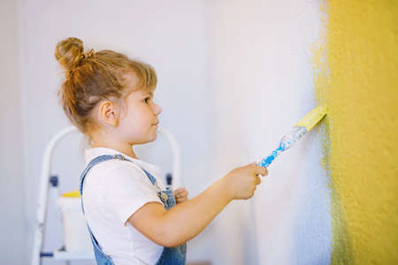Funny little toddler girl painting the wall with color in new house. Family repair apartment home. Happy baby child paints the wall, choosing color with palette, having fun with brush, indoors