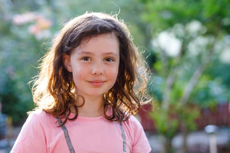 Portrait of little school girl. Happy smiling excited child on warm summer sunny day. Zdjęcie Seryjne