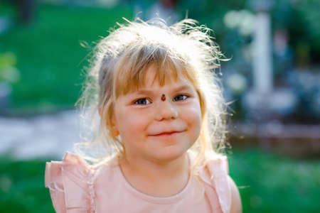 Portrait of little toddler girl with ladybug on face. Happy smiling excited child on warm summer sunny day.