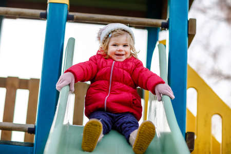 Cute toddler girl having fun on playground. Happy healthy little child climbing, swinging and sliding on different equipment. On cold day in colorful clothes. Active outdoors game for children Foto de archivo