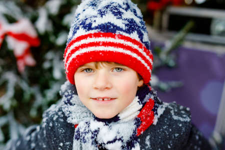 Funny little kid boy in colorful clothes playing outdoors during strong snowfall. Active leisure with children in winter on cold snowy days. Happy child having fun, playing with snow. Winter fashion.