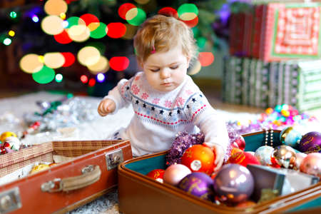 Adorable baby girl holding colorful lights garland in cute hands. Little child in festive clothes decorating Christmas tree with family. First celebration of traditional holiday called Weihnachten Foto de archivo