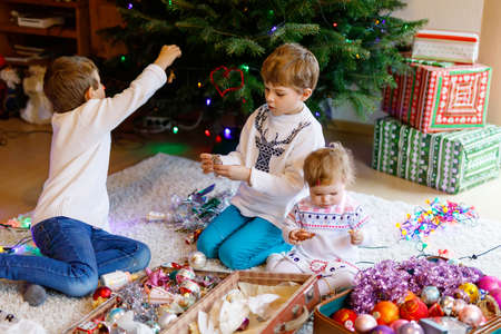 Two little kid boys and adorable baby girl decorating Christmas tree with old vintage toys and balls. Family preaparation celebration of family holiday. Three children, brothers and sister at home. Foto de archivo