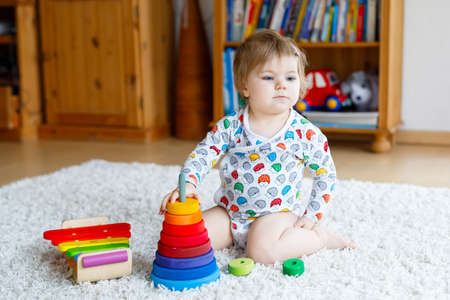 Adorable cute beautiful little baby girl playing with educational wooden toys at home or nursery. Toddler with colorful stack pyramid