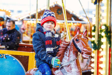 Adorable little kid boy riding on a merry go round carousel horse at Christmas funfair or market, outdoors. Happy child having fun on traditional family xmas market in Germany