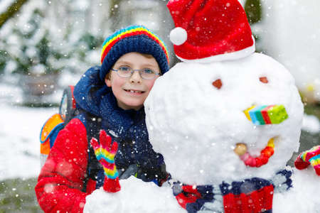 Little school kid boy in colorful clothes, with glasses and backpack having fun with snowman after elementary school end. Child playing with snow on winter day