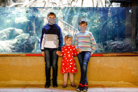 Two kids boys and toddler girl visiting together zoo aquarium. Three children watching fishes and jellyfishes. School boys wearing medicals masks due pandemic corona virus time. Family on staycation