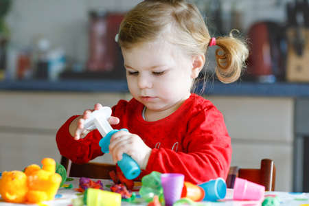 Adorable cute little toddler girl with colorful clay. Healthy baby child playing and creating toys from play dough. Small kid molding modeling clay and learning Banque d'images