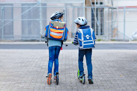 Two school kid boys in safety helmet riding with scooter in the city with backpack on sunny day. Happy children in colorful clothes biking on way to school. Banque d'images