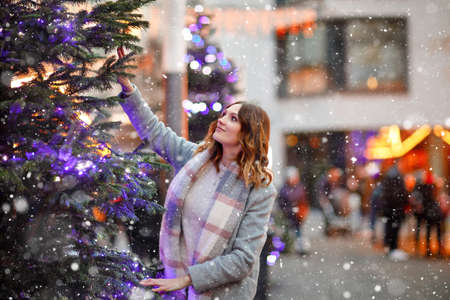Beautiful young woman having fun on traditional Christmas market during strong snowfall. Happy girl enjoying traditional family market in Germany. Lady standing by illuminated xmas tree.
