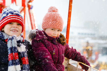 Two little kids, boy and girl having fun on ferris wheel on traditional German Christmas market during strong snowfall. Happy children enjoying family market in Germany. Lovely siblings.