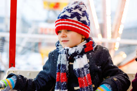 Little lovely kid boy having fun on ferris wheel on traditional German Christmas market during strong snowfall. Happy healthy child enjoying family market in Germany. Lovely schoolboy.